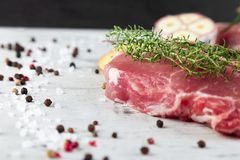 Raw pork meat with spice ingredient. Raw pork meat on black slate plate with spice ingredient - rosemary, ginger, chilli pepper, onion.Top view. Flat lay. Copy Stock Image