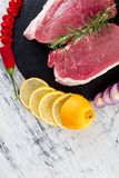 Raw pork meat with spice ingredient. Raw pork meat Tenderloin on black slate plate with spice ingredient - rosemary, ginger, chilli pepper, onion.Top view. Flat Royalty Free Stock Photo