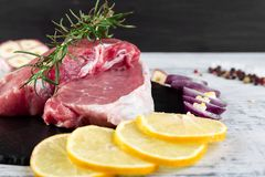 Raw pork meat with spice ingredient. Raw pork meat Tenderloin on black slate plate with spice ingredient - rosemary, ginger, chilli pepper, onion Royalty Free Stock Photography