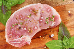 Raw pork meat with spices and herbs. Ready to cook on wooden board Royalty Free Stock Photo
