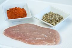 Raw pork meat with spices. Paprika and herbal salt Royalty Free Stock Images