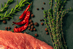 Raw pork meat with spices on slate stone kitchen board.  Stock Images