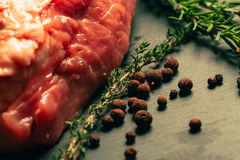 Raw pork meat with spices on slate stone kitchen board.  Stock Photography
