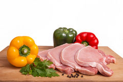 Raw pork meat, vegetables and spices, arranged on kitchen board. Selective focus, copy space Royalty Free Stock Photo