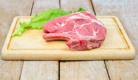 Raw pork meat on wooden board. Raw pork steak and lettuce leaf on wooden board Stock Photo
