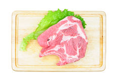 Raw pork meat on wooden board. Raw pork steak and lettuce leaf on wooden board, isolated Stock Photography