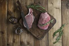 Raw pork meat on a wooden board and knife, spices and rosemary. royalty free stock photography