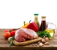 Raw pork meat on wooden desk. Raw pork meat with spices and vegetables isolated Royalty Free Stock Photos