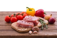 Raw pork meat on wooden desk. Raw pork meat with spices and vegetables on wooden table Stock Photography