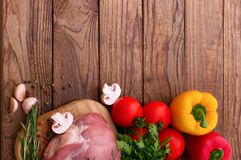 Raw pork meat on wooden desk. Raw pork meat with spices and vegetables on wooden table Stock Image