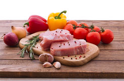 Raw pork meat on wooden desk. Raw pork meat with spices and vegetables on wooden table Royalty Free Stock Photography