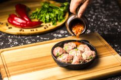 Raw pork meatballs in a black frying pan in tomato sauce royalty free stock images