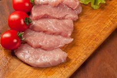 Raw pork оn the wood board. Tomato and lettice Royalty Free Stock Photo