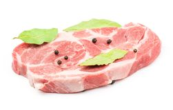 Raw pork neck cut isolated on white. Raw pork neck meat cut with black pepper and three bay leaves isolated on white background fresh one slice without bone Royalty Free Stock Photo