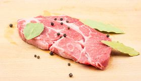 Raw pork neck cut isolated on white. Raw pork neck meat cut with black pepper and bay leaves on wood background fresh one slice without bone Stock Photo