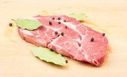 Raw pork neck cut isolated on white. Raw pork neck meat cut on wood background fresh one slice without bone with black pepper and bay leaves Royalty Free Stock Photography