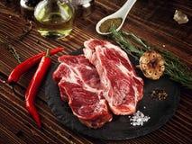 Raw pork neck steak on a stone plate. Stock Photo