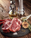 Raw pork neck steak on a stone plate. Stock Images