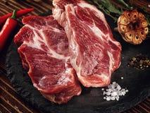 Raw pork neck steak on a stone plate. Royalty Free Stock Photo