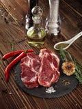 Raw pork neck steak on a stone plate. Royalty Free Stock Image