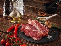 Raw pork neck steak on a stone plate. Royalty Free Stock Photos