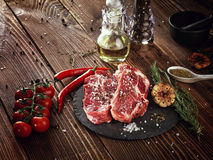 Raw pork neck steak on a stone plate. Royalty Free Stock Photography