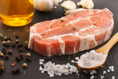 Raw pork neck with thyme, garlic, oil, pepper and salt Royalty Free Stock Photo