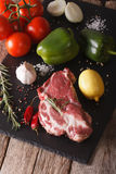 Raw pork neck and vegetables close-up on board. Vertical Royalty Free Stock Images