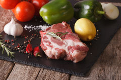 Raw pork neck and vegetables close up on a slate. Horizontal Royalty Free Stock Photography