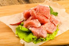 Raw pork pieces. With pepper and salt - ready for cooking Royalty Free Stock Images