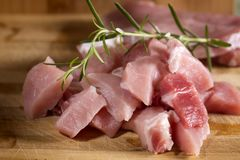 Raw pork ready to Cook on a wooden cutting board. Close up of some fresh pieces pork ready to Cook on a wooden cutting board Royalty Free Stock Photography