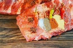 Raw pork rib chops cut board with chili pepper garlic and oil. Raw pork rib chops on cut board with chili pepper garlic and oil Royalty Free Stock Photo