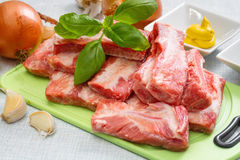 Raw pork ribs on a cutting board and  set of spices for cooking. Royalty Free Stock Image