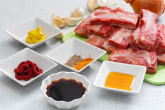Raw pork ribs on a cutting board and  set of spices for cooking. Stock Images