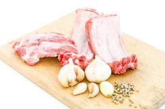 Raw pork ribs and garlic,pepper on a cutting board Royalty Free Stock Photos