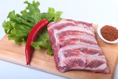 Raw pork ribs with herbs and spices on wooden board. Ready for cooking. Raw pork ribs with herbs and spices on wooden board. Ready for cooking Stock Image