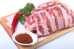 Raw pork ribs with herbs and spices on wooden board. Ready for cooking. Raw pork ribs with herbs and spices on wooden board. Ready for cooking Stock Photos