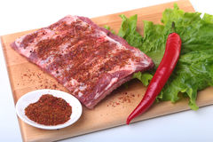 Raw pork ribs with herbs and spices on wooden board. Ready for cooking. Raw pork ribs with herbs and spices on wooden board. Ready for cooking Royalty Free Stock Images