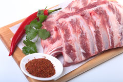 Raw pork ribs with herbs and spices on wooden board. Ready for cooking. Raw pork ribs with herbs and spices on wooden board. Ready for cooking Stock Photo