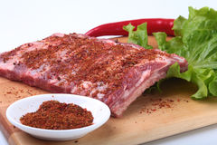 Raw pork ribs with herbs and spices on wooden board. Ready for cooking. Raw pork ribs with herbs and spices on wooden board. Ready for cooking Royalty Free Stock Image