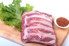 Raw pork ribs with herbs and spices on wooden board. Ready for cooking. Raw pork ribs with herbs and spices on wooden board. Ready for cooking Royalty Free Stock Photos
