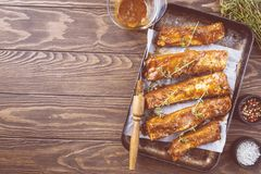 Raw pork ribs. Pickled in sauce with thyme on a dark wooden background, top view Stock Images