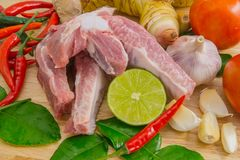 Raw pork ribs with vegetables on wooden cutting board. Close up Raw pork ribs with vegetables on wooden cutting board Stock Photos