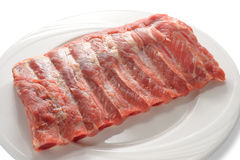 Raw pork ribs. On white plate royalty free stock images