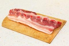 Raw pork ribs on wooden cutting board. Raw pork ribs on wooden cutting board taken closeup Stock Photos