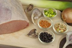 Raw pork roast. Fresh raw pork on a cutting board with vegetables and spices, preparation of meat for grilling Stock Images