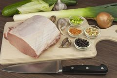 Raw pork roast. Fresh raw pork on a cutting board with vegetables and spices, preparation of meat for grilling Stock Photos