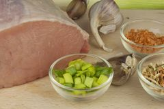 Raw pork roast. Fresh raw pork on a cutting board with vegetables and spices, preparation of meat for grilling Royalty Free Stock Photos