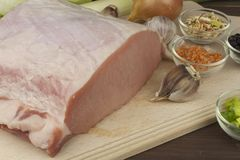 Raw pork roast. Fresh raw pork on a cutting board with vegetables and spices, preparation of meat for grilling Royalty Free Stock Photography