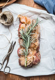 Raw Pork roast on white backing paper with rope and shears, cooking preparation, top view. Close up Stock Photos